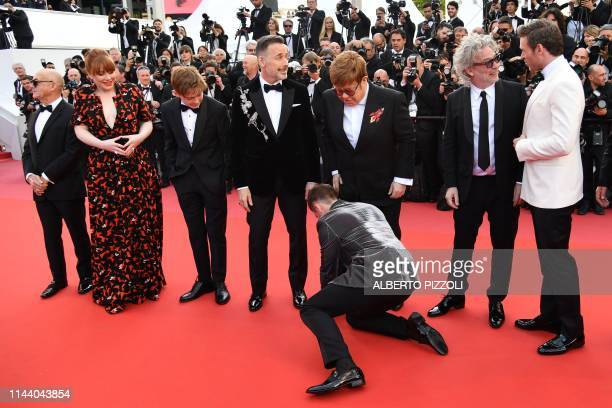 British actor Taron Egerton ties British singersongwriter Elton John's shoe laces as they arrive with British songwriter Bernie Taupin US actress...