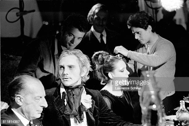 British actor Terence Stamp and others sit at a table during production of 'Toby Dammit' one section of the anthology film 'Spirits of the Dead' Rome...