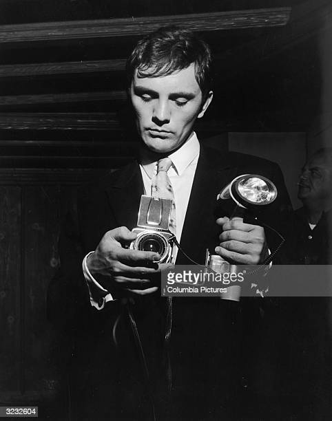 British actor Terence Stamp prepares to take a photograph in a still from director William Wyler's film 'The Collector'