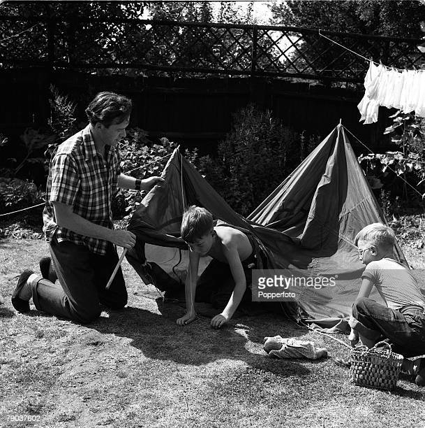 British actor Tony Britton erecting a tent in his garden for two young boys England 3rd September 1955