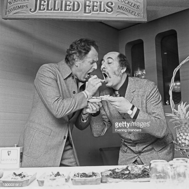 British actor-manager Brian Rix and actor Alfred Marks feeding each other seafood under a sign for 'Jellied Eels', UK, 27th January 1972. They are...