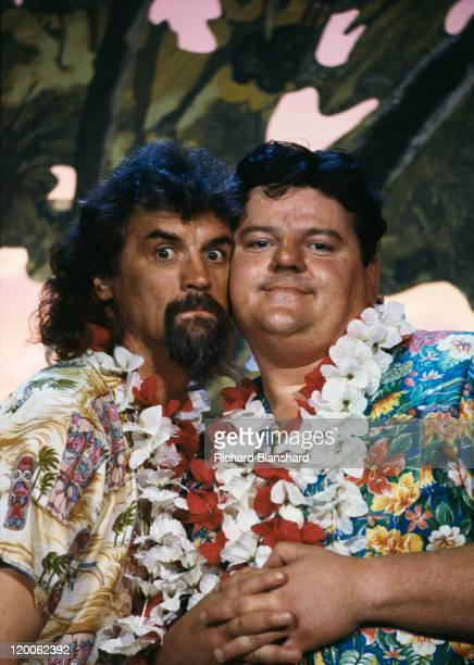 British actors Billy Connolly and Robbie Coltrane wearing Hawaiian shirts and leis circa 1990