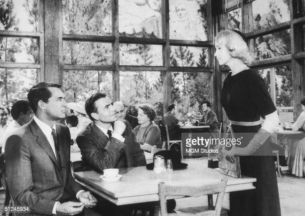 1959 British actors Cary Grant and James Mason look up from their table toward American actor Eva Marie Saint in the dining room below Mount Rushmore...
