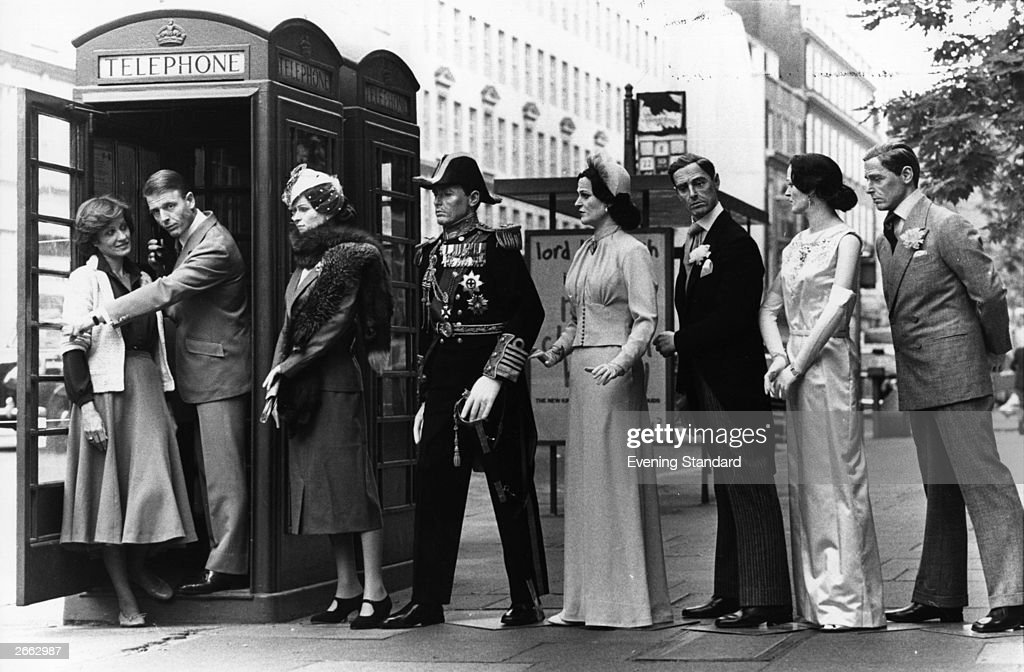 British actors Edward Fox and Cynthia Harris, stars of Thames TV series Edward and Mrs Simpson, pose in the doorway of a telephone box with life-size models of Mrs Simpson and Edward VIII in line behind them at the Kodak Gallery in London where an exhibition of prints taken on location is being shown. Original Publication: People Disc - HD0113