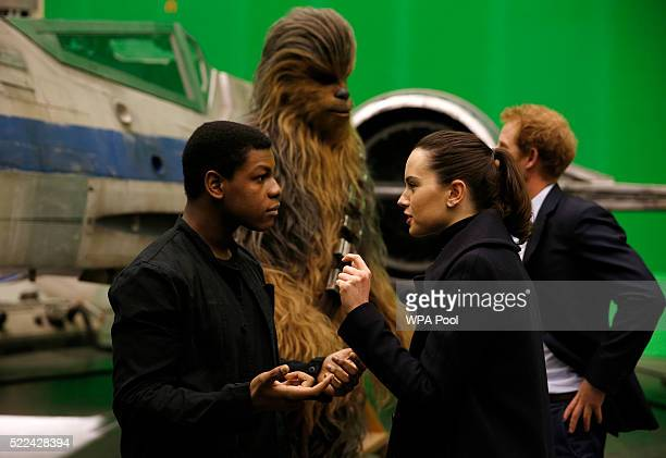 British actors John Boyega and Daisy Ridley speak to each other as Prince Harry talks with Chewbacca in the background during tour of the Star Wars...