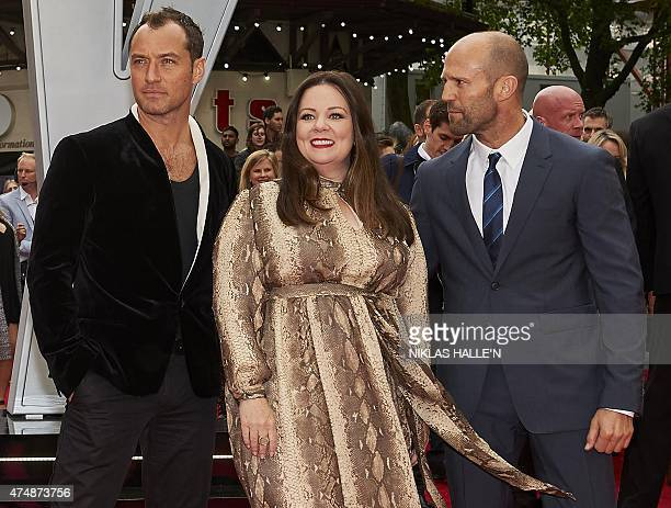 British actors Jude Law US actress Melissa McCarthy and British actor Jason Statham pose for photographs on the carpet as they arrive to attend the...