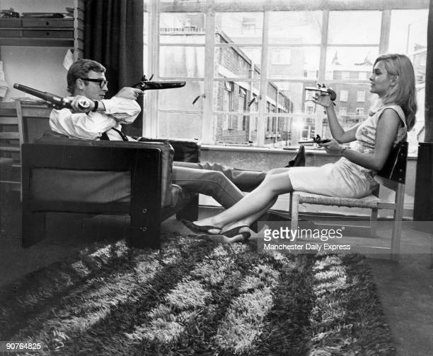 British actors Michael Caine and Alexandra Bastedo aim pistols at each other