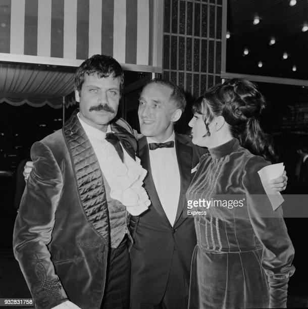 British actors Oliver Reed and Ron Moody and a guest attend the premiere of musical drama film 'Oliver' UK 26th September 1968