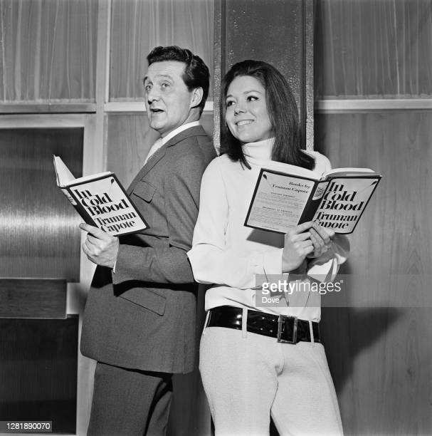 British actors Patrick Macnee and Diana Rigg , both reading the Truman Capote bestseller 'In Cold Blood' at London Airport, UK, 12th March 1966. They...