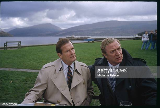 British actors Roger Moore and Michael Caine brave typically gray Scottish weather conditions for the shooting of Michael Winner's film, Bullseye.
