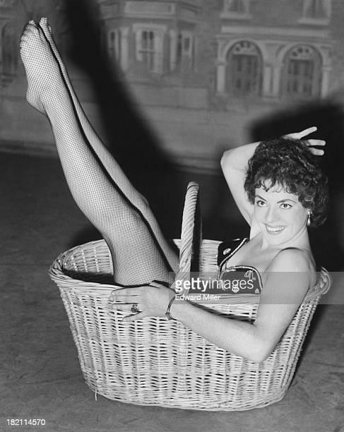 British actress and dancer Anne Hart poses in a basket during rehearsals of the 'Crazy Gang' show 'Clown Jewels' at the Victoria Palace Theatre...
