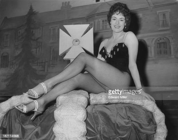 British actress and dancer Anne Hart sits on a large prop crown during rehearsals for the 'Crazy Gang' show 'Clown Jewels' at the Victoria Palace...