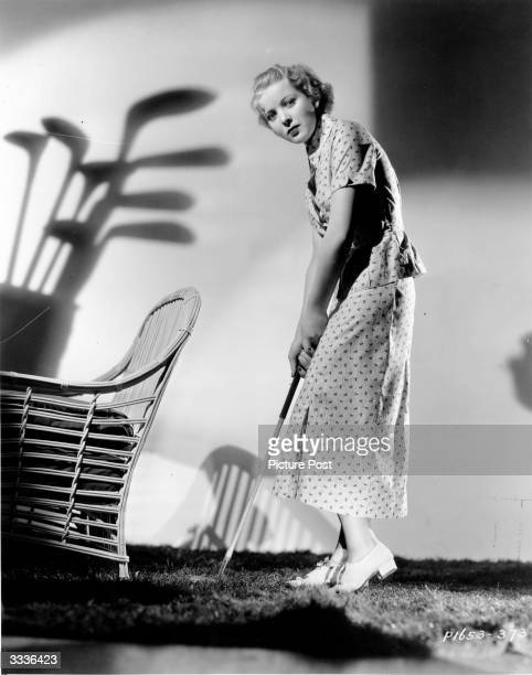British actress and future film director Ida Lupino holding a golf club on fake turf whilst in costume for 'Paris in Spring' a Paramount Pictures...