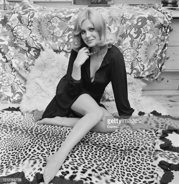 British actress and model Joanna Lumley poses holding her bead necklace as she sits on a leopard skin rug 18th September 1972