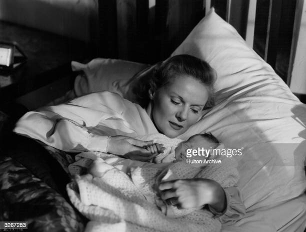 British actress Ann Todd who was married to director David Lean lies in bed with her screen baby in a scene from the film 'The Sound Barrier' written...