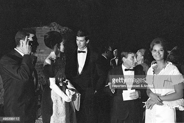 British actress Audrey Hepburn American actor Anthony Perkins Italian singersongwriter Renato Rascel and Italian actress Lea Massari chatting at...