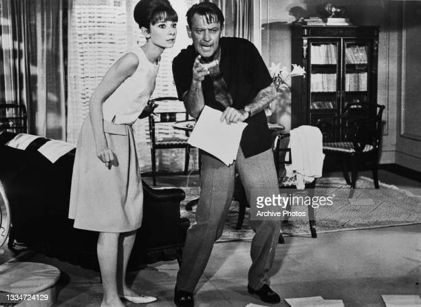 British actress Audrey Hepburn beside American actor William Holden who has an angry expression on his face in a scene from 'Paris When It Sizzles,'...