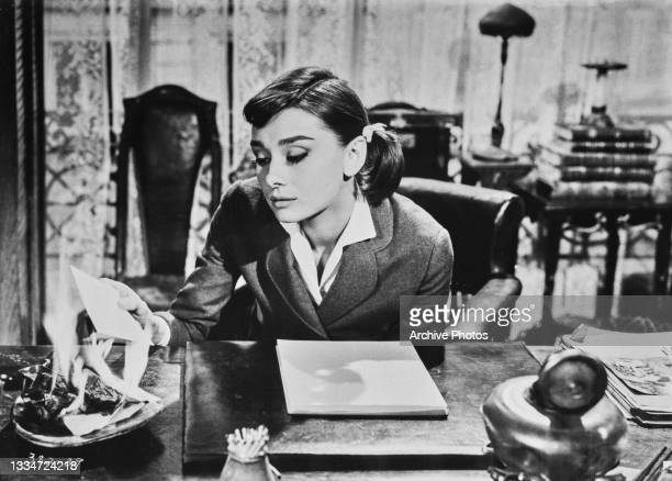 British actress Audrey Hepburn burning a letter in a dish on a desk in a scene from 'Love in the Afternoon' in which Hepburn plays Ariane Chavasse,...