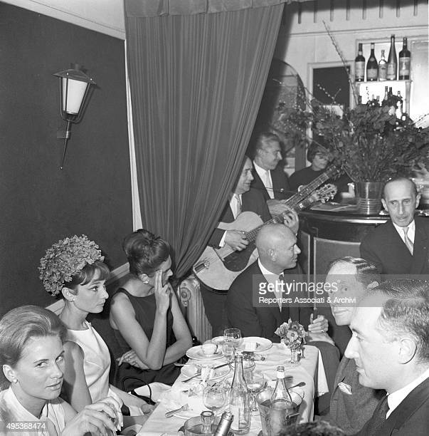 British actress Audrey Hepburn dining at the restaurant in Paris with her husband and American director actor and film producer Mel Ferrer and...