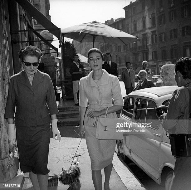 British actress Audrey Hepburn leading her dog by the leash while walking with her mother, the Dutch baroness Ella Van Heemstra. Rome, 1950s.