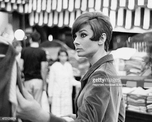 'British actress Audrey Hepburn observes with the critical eye a dress hung into a store full of fabrics she's in France for the shooting of her last...