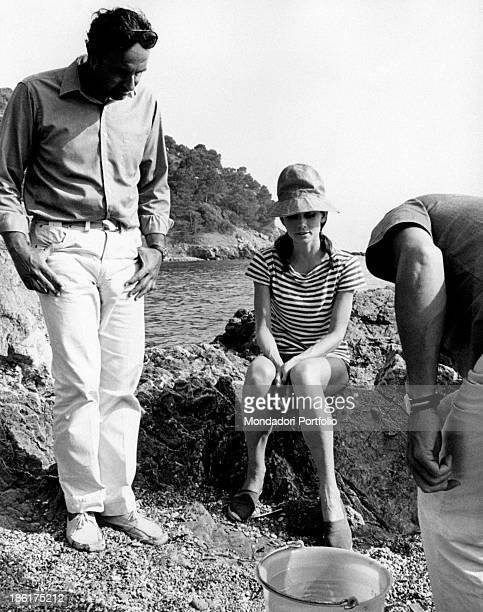 British actress Audrey Hepburn sitting on a rock beside American director Stanley Donen on the set of the film Two for the Road August 1966