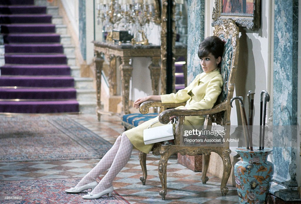 British actress Audrey Hepburn (Audrey Kathleen Ruston) sitting on an old chair in the film How to Steal a Million. 1966