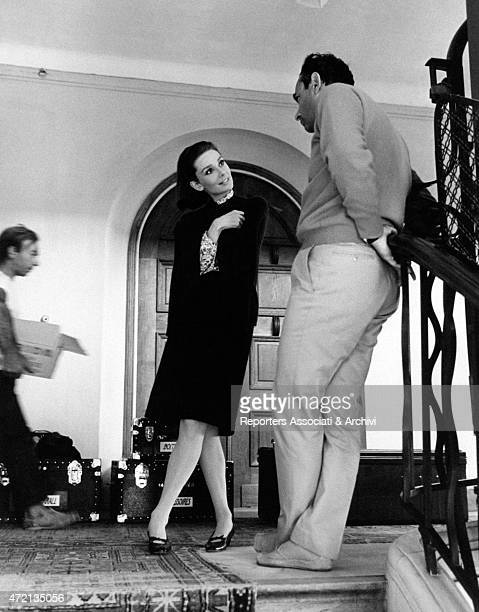 British actress Audrey Hepburn talking to American director Stanley Donen leaned against the handrail of a staircase on the set of the film Two for...