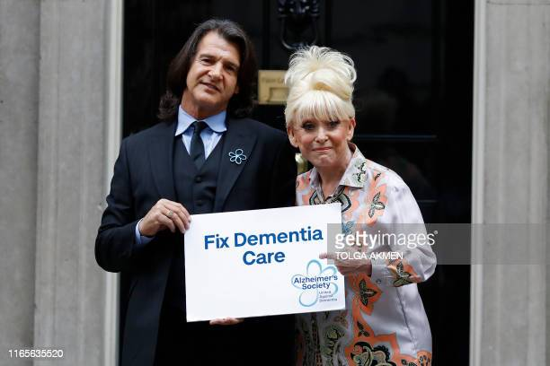 British actress Barbara Windsor and her husband Scott Mitchell pose outside 10 Downing Street as she delivers a petition calling for urgent action on...