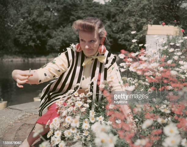 British actress Beryl Reid , wearing a black-and-white striped waistcoat over a polka dots top, with baubles hanging from her ears, with flowers in...