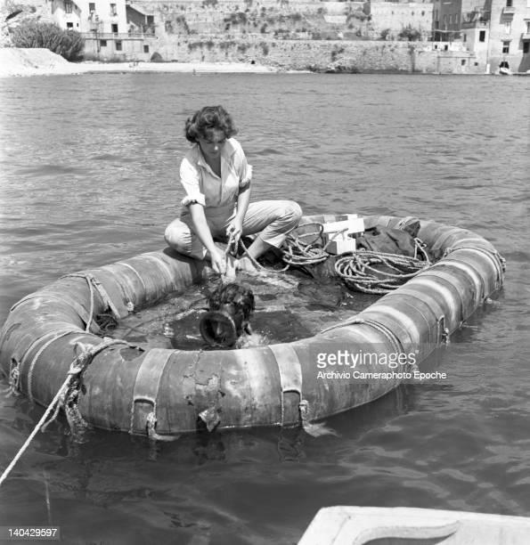 British actress Dawn Addams sitting on a rubber dinghy on the Mizar movie set 1953