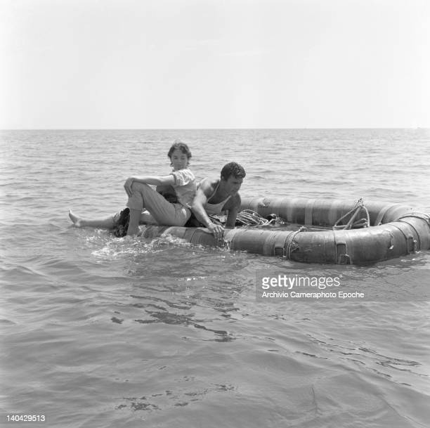 British actress Dawn Addams sitting on a rubber dinghy with Franco Silva on the Mizar movie set 1953