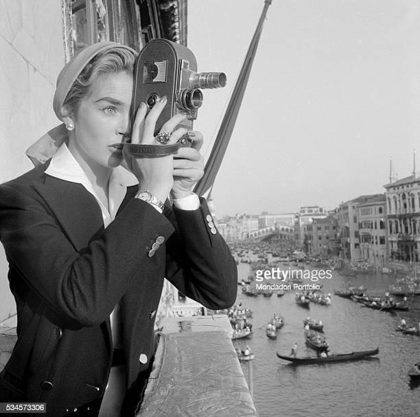 British actress Dawn Addams with a portable camera filming the Historical Regatta during the XVI Venice International Film Festival Venice 1955