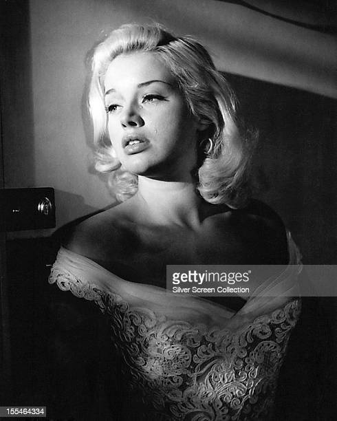 British actress Diana Dors sheds a tear in a promotional portrait, circa 1955. She is wearing an off-the-shoulder dress in white lace.
