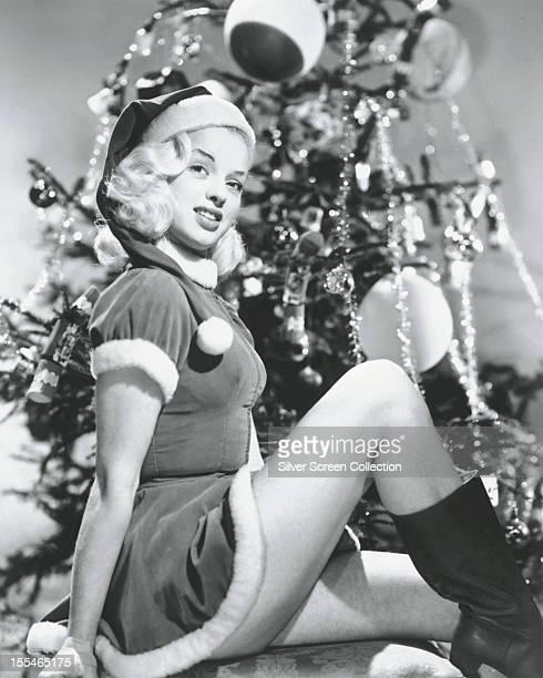 British actress Diana Dors sitting by a Christmas tree, wearing a santa outfit, circa 1955.