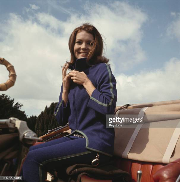 British actress Diana Rigg wearing a blue tracksuit with green trim, holding a cigarette while seating in the driver's seat of a car during filming...