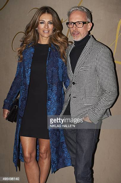 British actress Elizabeth Hurley and CanadianBritish designer Patrick Cox pose on arrival for the premiere of the Burberry festive film in London on...