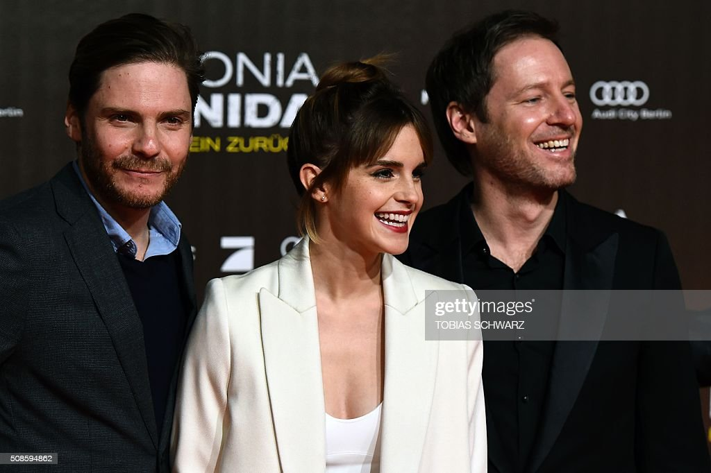 British actress Emma Watson (C), German actor Daniel Bruehl (L) and German director Florian Gallenberger pose for photographers on the red carpet ahead of the premiere of the film Colonia Dignidad in Berlin on February 5, 2016. / AFP / TOBIAS