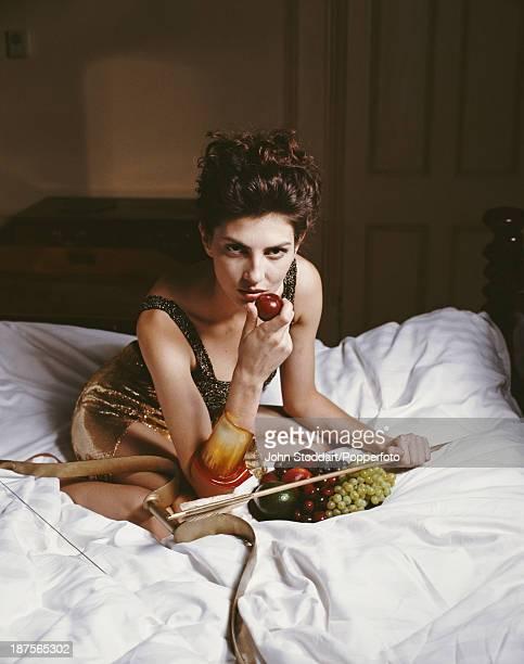 British actress Gina Bellman poses on a bed 1989
