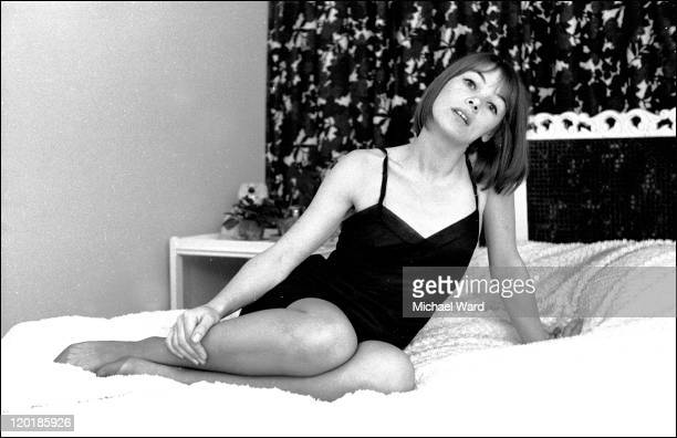 British actress Glenda Jackson wearing a negligee and reclining on a bed, 1964.