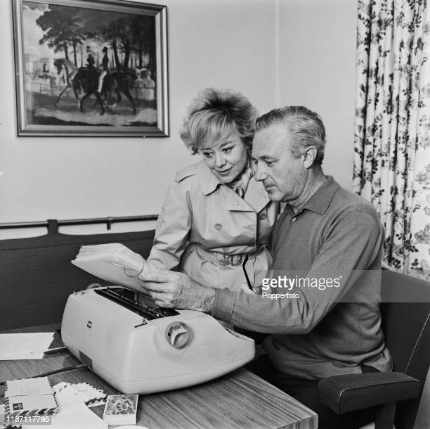 British actress Glynis Johns with her husband writer and novelist Elliot Arnold with a typewriter seated at a writing desk in England in August 1966