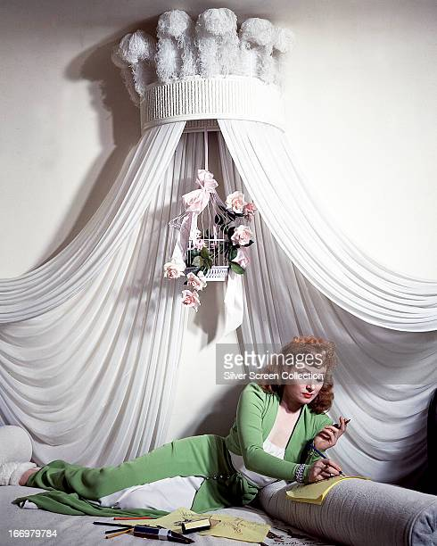 British actress Greer Garson drawing with coloured pencils as she reclines under a white canopy in a full length green and white outfit circa 1940