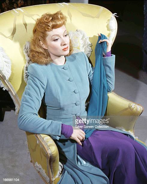 British actress Greer Garson sitting in an armchair in a powder blue and purple outfit circa 1940