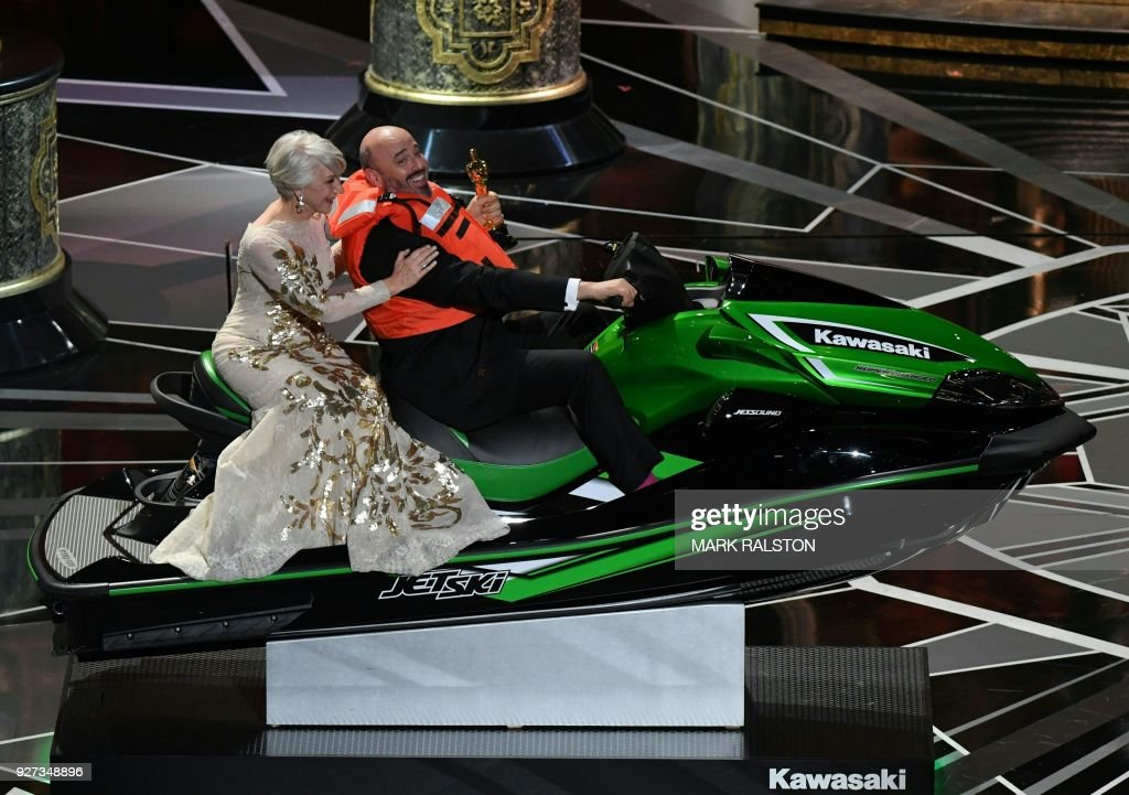 British actress Helen Mirren (L) rides with jet ski winner and laureate for Costume Design Mark Bridges after the Oscar ceremony host offered a jet ski to the Oscars winner with the shortest speech during the 90th Annual Academy Awards show on March 4, 2018 in Hollywood, California. / AFP PHOTO / Mark RALSTON