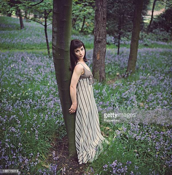 British actress Jacqueline Pearce wearing a grey and white striped mazi dress poses in a wood full of bluebells 1968