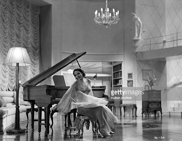 British actress Jessie Matthews wearing a romantic evening dress in a scene from the film 'Evergreen' directed by Victor Saville for Gaumont