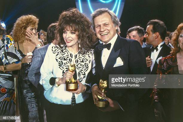 British actress Joan Collins and American actor Ken Kercheval showing smiling the Telegatto award won at the 3rd edition of Telegatto Television...