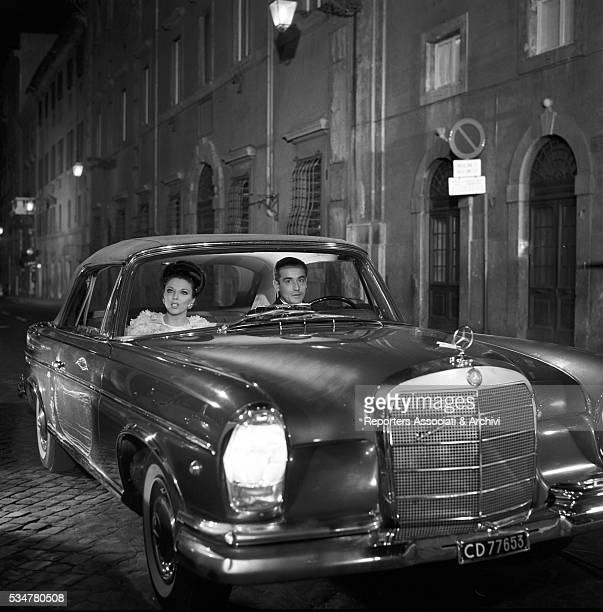 British actress Joan Collins and Italian actor Vittorio Gassman driving a Mercedes on the set of Hard Times for Princes Italy 1964
