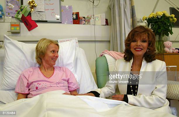 British actress Joan Collins visits cancer wards and serves tea to patient Allison Miller at The Royal Marsden Hospital on March 22 2004 in London...