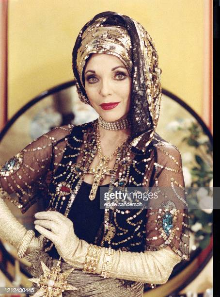 British Actress Joan Collins wearing gold lace and glitter with oversize jewelry during the filming of Decadence, a 1994 British film shot in...